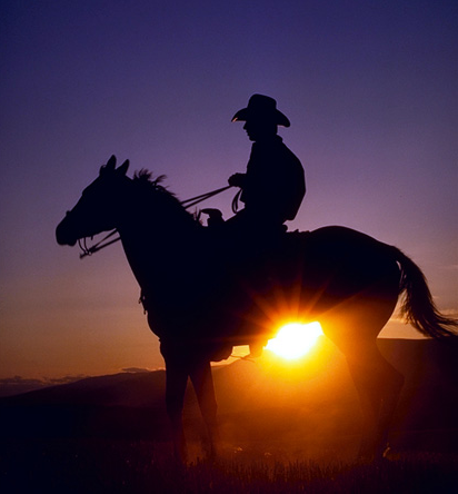 Cowboy on horse at sunrise.